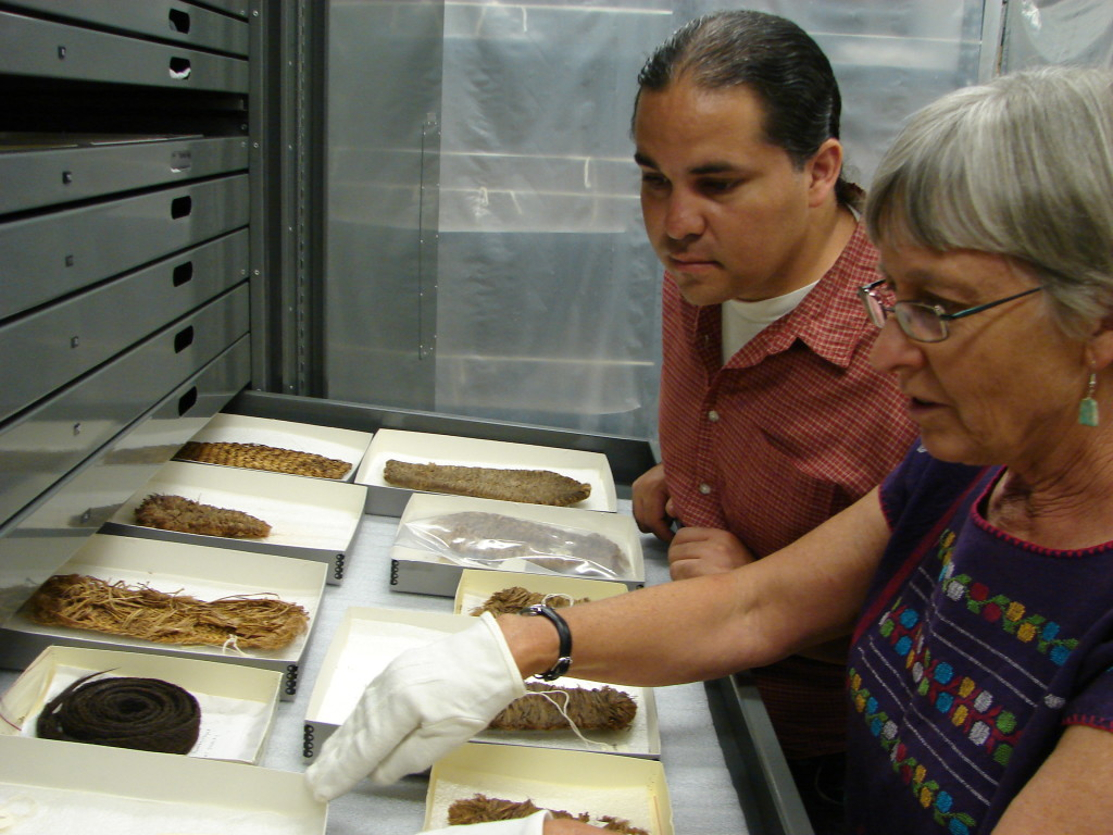 Team members Luis Garcia and Laurie Webster examining prehistoric sandals and a belt at the Edge of the Cedars Museum.